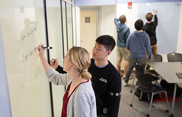 Bryant students in the College of Arts and Sciences write on a whiteboard