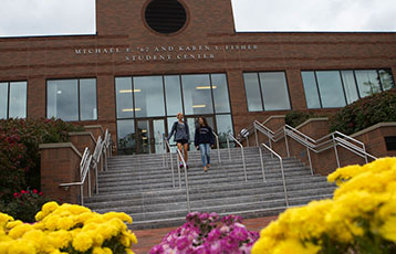Students walk down the stairs at the Fisher Student Center at Bryant University