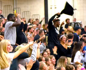 A group of students cheers on the Bryant men's basketball team