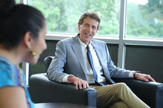 President Gittell sitting in library and talking with faculty
